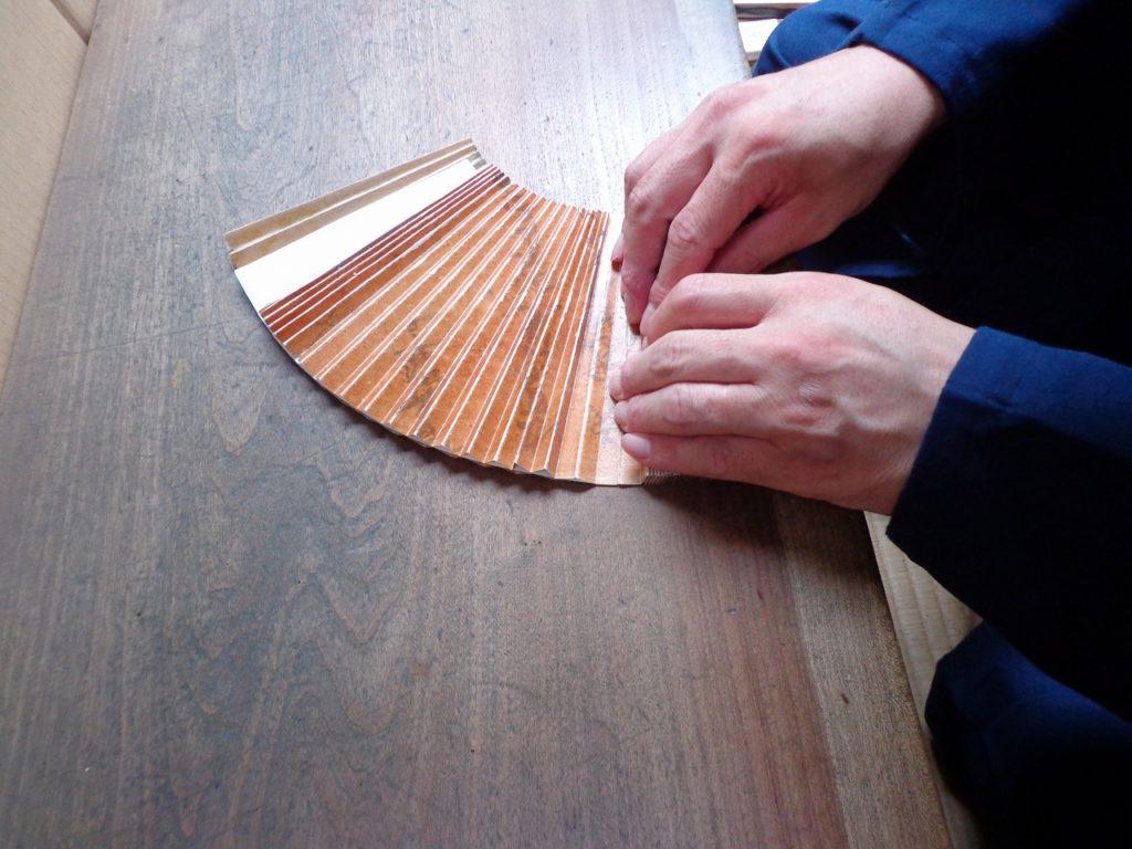湿しを加えて柔らかくした扇面を、型紙と言われる凹凸の二枚組の柿渋で硬くしたものの間に挟んで端から折り、扇子の骨の通る穴を端からあけてゆきます。