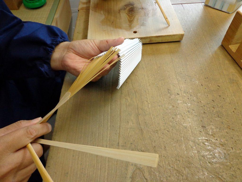 折りあがった扇面を折り地と言いますが、その折り地に糊を付けた扇骨を差し込んでゆきます。